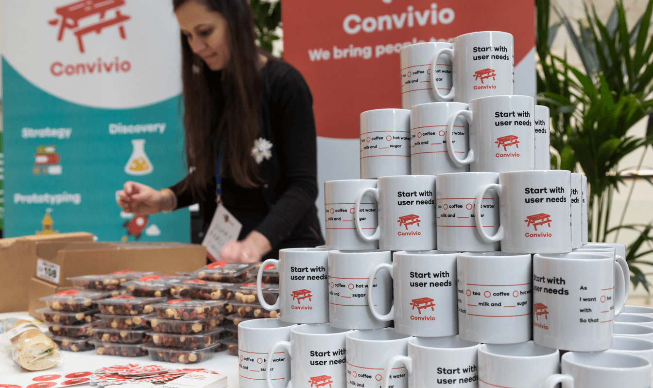 A photograph of a Convivio trade stand with a pile of mugs and banners in the background